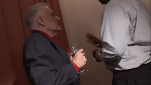 an elderly businessman hands a wad of cash to another man drinking a glass of wine at a party. - bribing stock videos & royalty-free footage