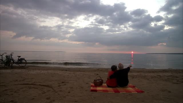 vídeos y material grabado en eventos de stock de an elderly couple having a picnic by the sea sweden. - manta ropa de cama