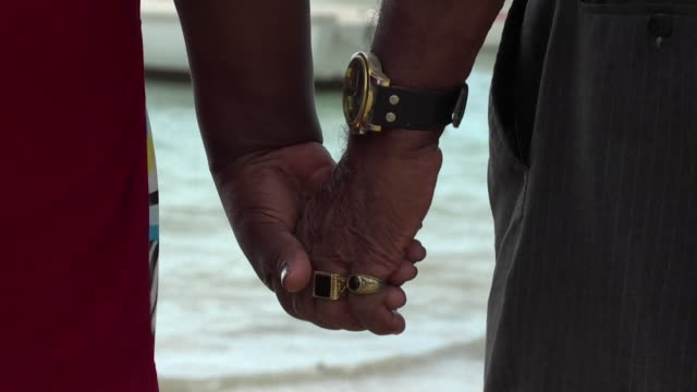 an elderly couple hold hands on a mauritian beach - couple relationship stock videos & royalty-free footage