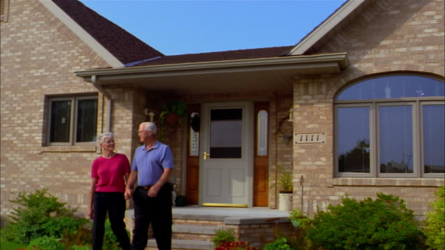 An elderly couple holds hands and walks away from a house.