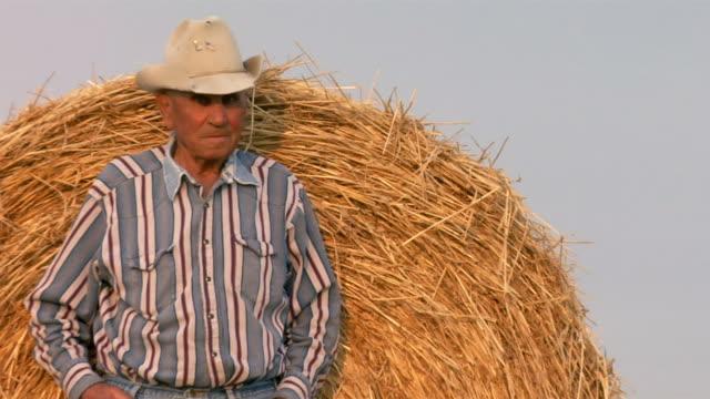 An elderly cowboy leans against a hay roll.