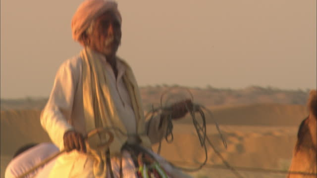 an elderly east indian man rides his camel across the desert. - camel stock videos & royalty-free footage