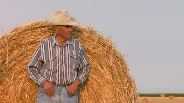 vidéos et rushes de an elderly farmer in a cowboy hat leans against a hay roll. - dakota du nord