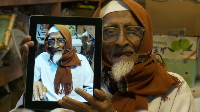 An elderly fruit vendor holds an iPad with a picture of himself on it.