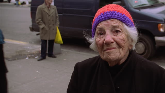 an elderly lady shrugs her shoulders near a street in new york. available in hd. - shrugging stock videos and b-roll footage