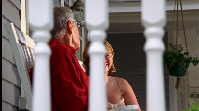 vídeos de stock e filmes b-roll de an elderly man and a woman visit in rocking chairs on a porch. - família com um filho