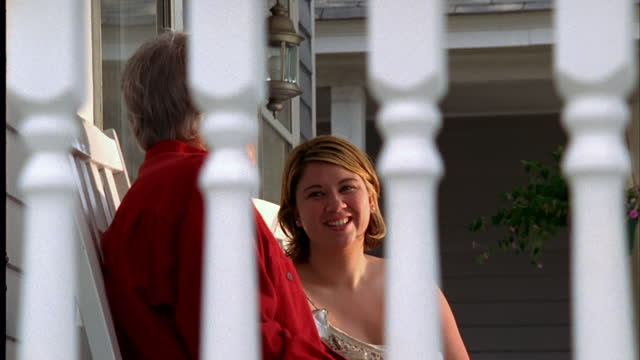 An elderly man and a woman visit on a front porch.