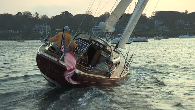 an elderly man and his crew sail a beautiful morris m42 sailboat and tack near jamestown. - jamestown stock-videos und b-roll-filmmaterial