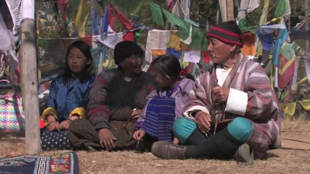 an elderly man and women holding prayer beads, and two young girls, seated in front of prayer flags. - prayer beads stock videos & royalty-free footage