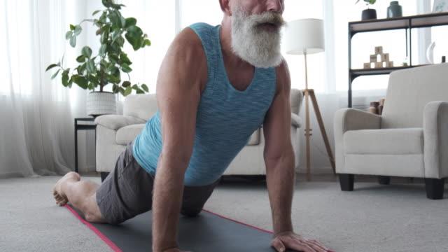 vídeos de stock, filmes e b-roll de um homem idoso fazendo exercícios esportivos em casa em auto-isolamento - atleta