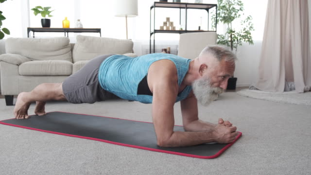 an elderly man doing sports exercises at home on self-isolation.slow motion - facial hair stock videos & royalty-free footage