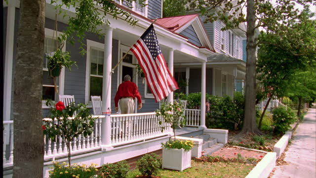 stockvideo's en b-roll-footage met an elderly man hangs an american flag from a porch. - gevel