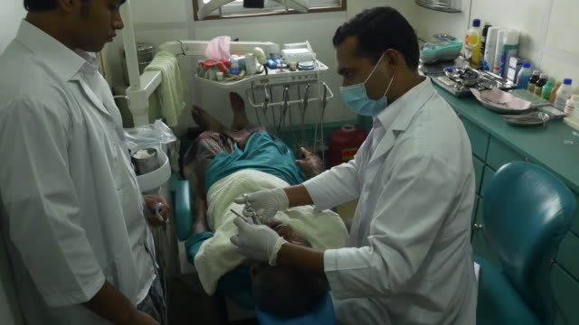 An elderly man is given free dental treatment in rural Bangladesh at a clinic operated on a hospital ship by a healthcare NGO