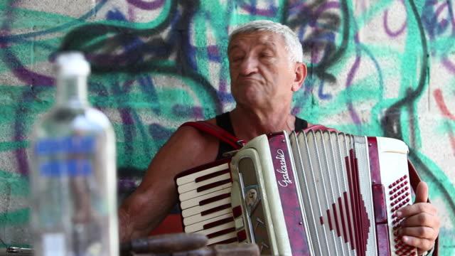 vídeos y material grabado en eventos de stock de an elderly man plays the accordion in front of a graffiti wall. - acordeonista