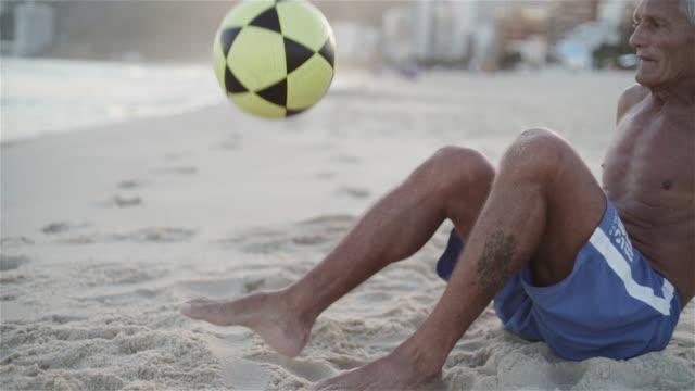 cu an elderly man plays with a football lying on ipanema beach / rio de janeiro, brazil - calciare video stock e b–roll