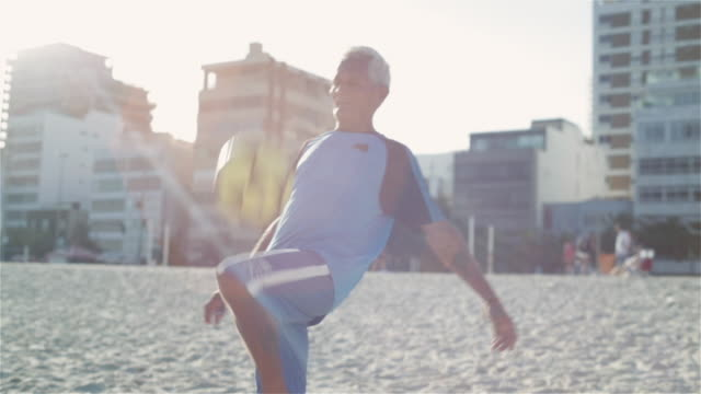stockvideo's en b-roll-footage met ms, tu an elderly man practices his football skills on ipanema beach / rio de janeiro, brazil - schoppen lichaamsbeweging