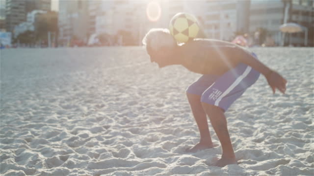 MS, TU An elderly man practices his football skills on Ipanema beach / Rio de Janeiro, Brazil