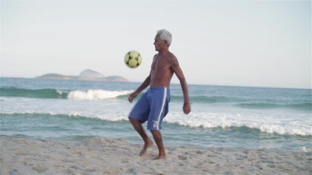 vídeos de stock, filmes e b-roll de ws an elderly man practices his football skills on ipanema beach / rio de janeiro, brazil - termo esportivo