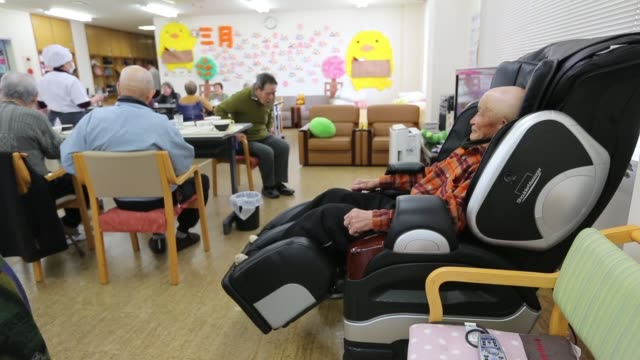 an elderly man sits in reclining chair at a day care center in the rural gogo island in matsuyama, ehime prefecture, elderly people move around at a... - zurücklehnen stock-videos und b-roll-filmmaterial