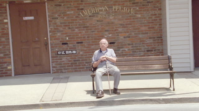 an elderly man sits on a bench in front of an american legion building. - panchina video stock e b–roll