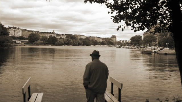 stockvideo's en b-roll-footage met an elderly man standing on a jetty stockholm sweden. - sepiakleurig