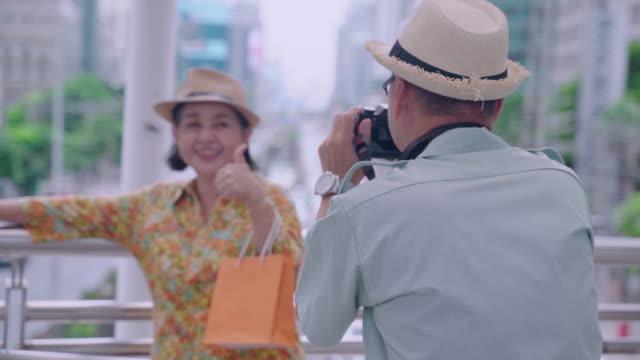 ファンと一緒に写真を撮る年配の男性は、タイの首都を見下ろすテラスの歩道でポーズをとります。 - travel点の映像素材/bロール