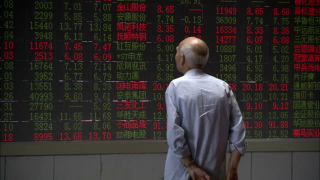 An elderly man watches a stock ticker, China. Available in HD.