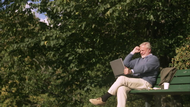 an elderly man with a computer in a park sweden. - silver surfer stock videos & royalty-free footage