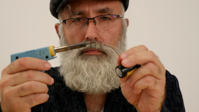 an elderly man with a white beard solder - beard stock videos & royalty-free footage