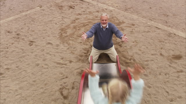 stockvideo's en b-roll-footage met an elderly man with granddaughter in a playground sweden. - glijbaan speeltuintoestellen