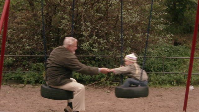 vídeos de stock, filmes e b-roll de an elderly man with granddaughter in a playground sweden. - boina