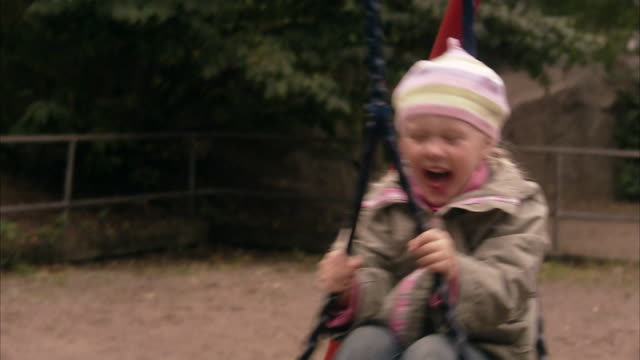 an elderly man with granddaughter in a playground sweden. - tyre swing stock videos & royalty-free footage