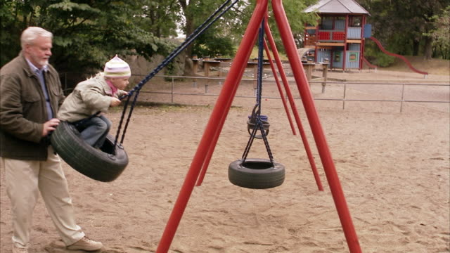an elderly man with granddaughter in a playground sweden. - sweden stock videos & royalty-free footage