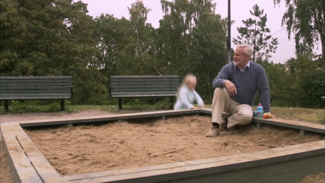vidéos et rushes de an elderly man with granddaughter in a playground sweden. - 2 kid in a sandbox