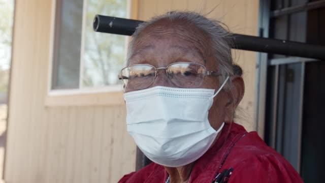 vídeos de stock, filmes e b-roll de uma avó navajo idosa e matriarca em sua casa, usando uma máscara para protegê-la do coronavírus - tribo norte americana