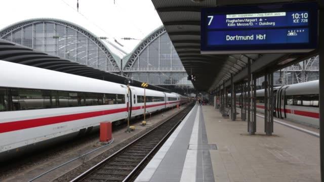 an elderly passenger walks past a deutsche bahn ag intercity express train, manufactured by siemens ag, at frankfurt central station in frankfurt,... - 高速列車点の映像素材/bロール