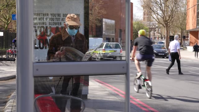 an elderly person wears personal protection equipment at a transport for london bus stop during the coronavirus covid-19 pandemic. - old stock videos & royalty-free footage
