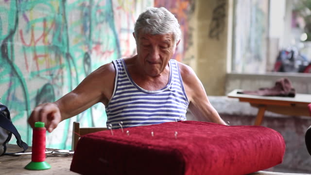An elderly upholsterer works on a cushion on a Tel Aviv street corner.