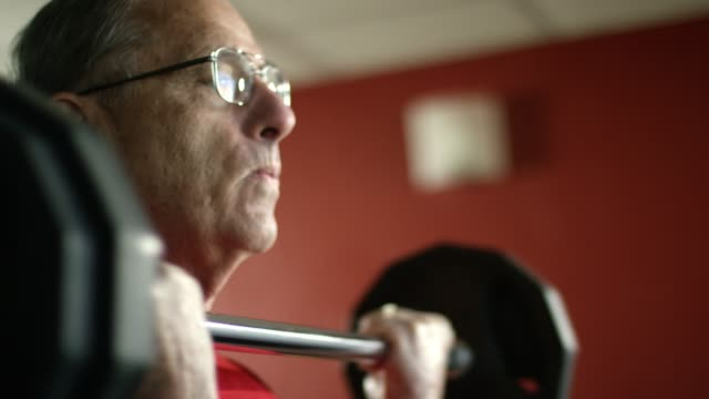 an elderly white man weight lifts with a barbell at a gym - weight training stock videos & royalty-free footage