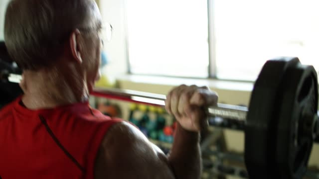 An Elderly White Man Weight Lifts with a Barbell at a Gym