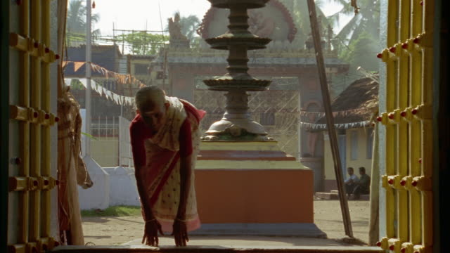 an elderly woman bows and puts her hands together in prayer before entering a temple. - respect stock videos and b-roll footage