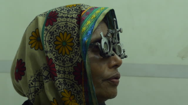 An elderly woman has an eye examination and test by an optician before being given new glasses by a healthcare NGO in rural Bangladesh operating from a hospital ship