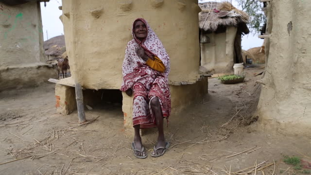 ws of an elderly woman in a colourful sari who is sitting outside in front of mud hut in a rural area in a village near birgunj a border town in... - strohdach stock-videos und b-roll-filmmaterial