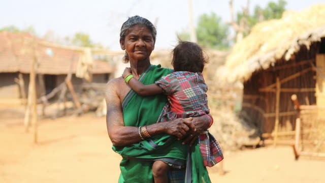 CU ZO of an elderly woman in a green sari who is carrying a child while she is standing on a farm track in a rural area of the village Satia a small...