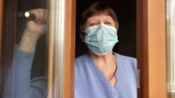 An elderly woman in a medical mask opens a window in a hospital. Quarantine self-isolation, coronavirus.