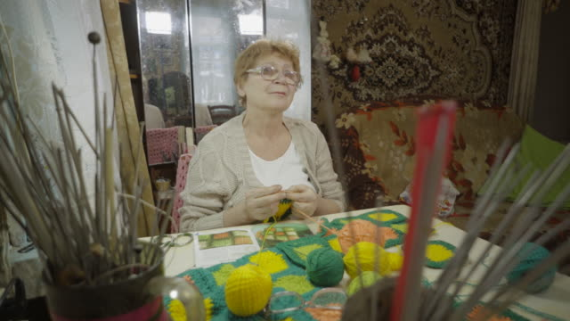 An elderly woman knitting floor mat, using needles and woolen yarn, sitting by the window in a rustic house.