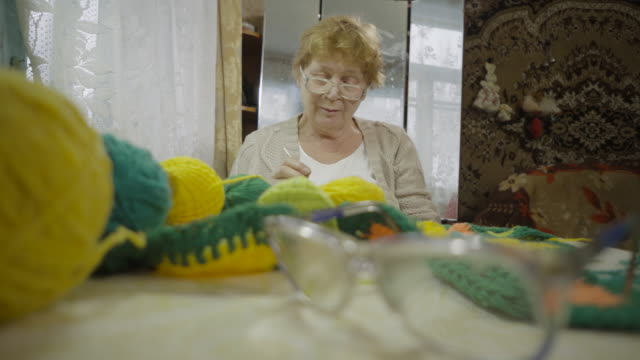 an elderly woman knitting floor mat, using needles and woolen yarn, sitting by the window in a rustic house. - stricken stock-videos und b-roll-filmmaterial