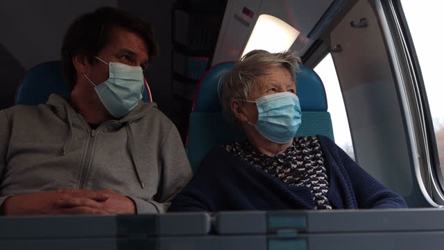 an elderly woman on a train with a protective mask accompanied by her son to join his family for the christmas holidays on december 17, 2020 in... - grey hair stock videos & royalty-free footage