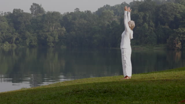 An elderly woman practices yoga beside a lake.
