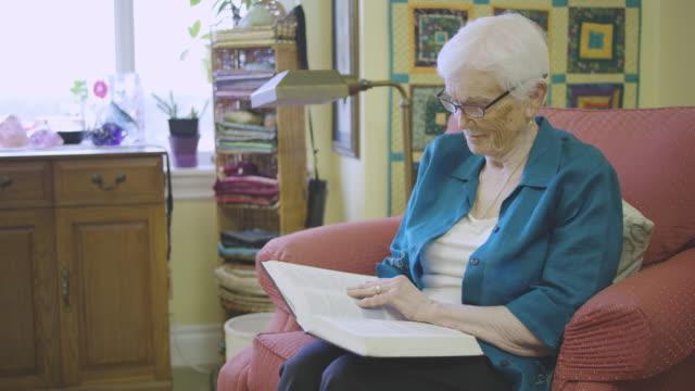 stockvideo's en b-roll-footage met een oudere vrouw lezen van de bijbel in een zorg-faciliteit - gemengde leeftijdscategorie